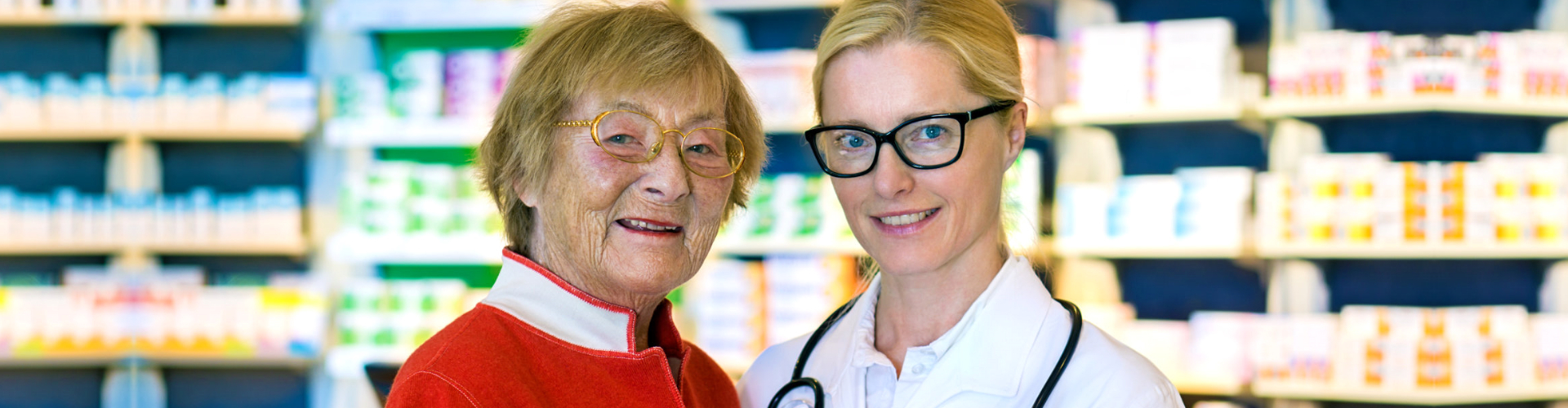 happy older women holding hands with smiling young female doctor